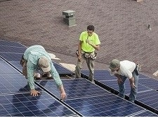 Workers install solar panels on a youth opportunity center
